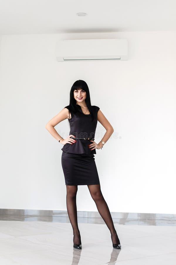 A mulher moreno feliz bonita nova vestida em um terno de negócio preto com uma saia curto está estando contra a parede branca den fotografia de stock royalty free