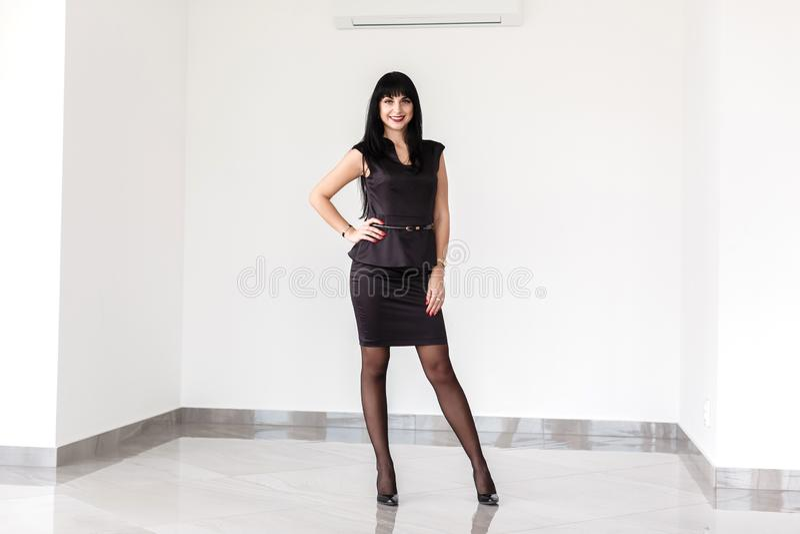 A mulher moreno feliz bonita nova vestida em um terno de negócio preto com uma saia curto está estando contra a parede branca den fotografia de stock