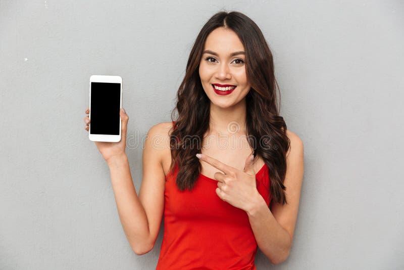 Mulher moreno feliz na roupa ocasional que mostra a tela vazia do smartphone foto de stock