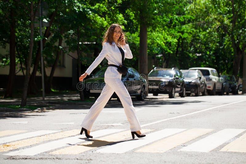 Mulher moreno feliz nova no terno de negócio branco imagem de stock