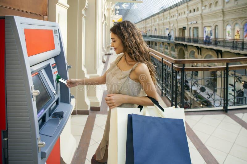 Mulher moreno feliz nova que retira o dinheiro do cartão de crédito em imagem de stock royalty free