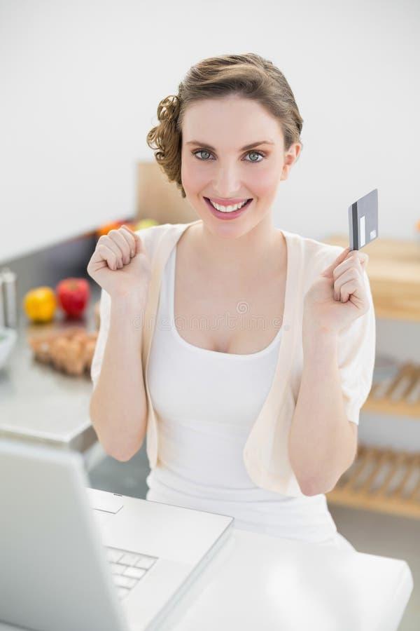Mulher moreno feliz que senta-se na cozinha quando compras ao domicílio foto de stock royalty free