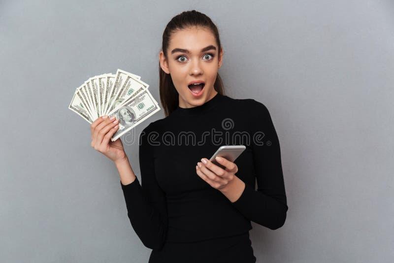 Mulher moreno feliz surpreendida na roupa preta que guarda o dinheiro fotos de stock