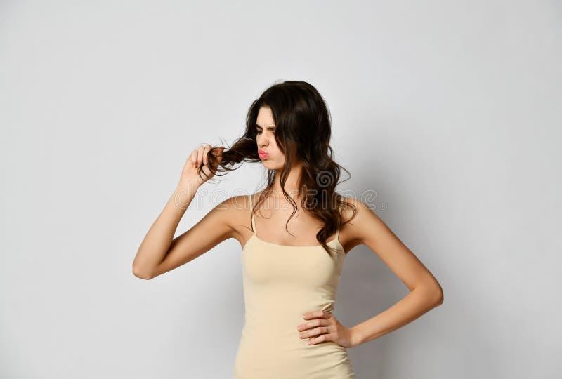 Mulher moreno frustrante que examina o cabelo danificado seco sobre o cinza imagem de stock