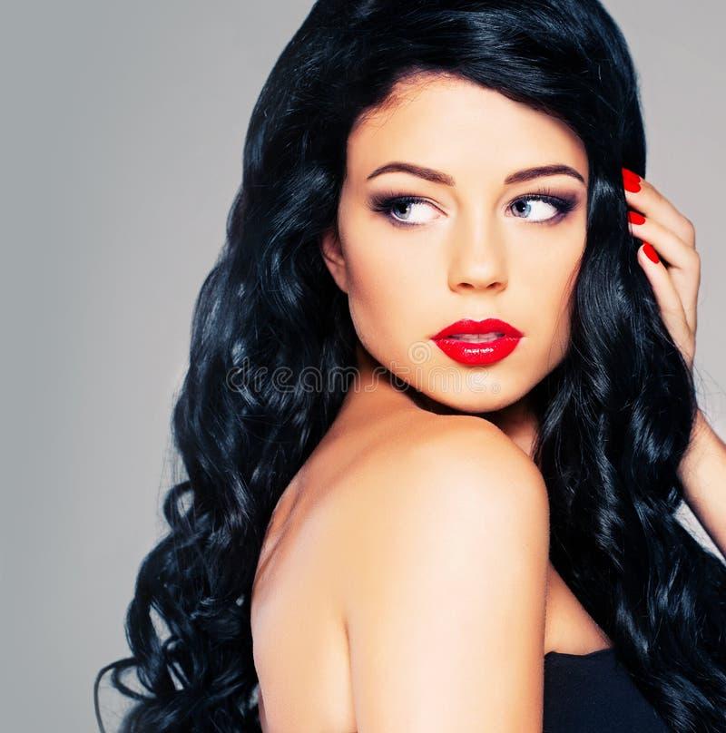 Mulher moreno glamoroso com cabelo encaracolado e composição vermelha dos bordos fotografia de stock