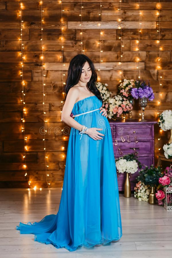 Mulher moreno grávida bonita em um vestido azul de seda longo que está na altura e em olhares completos na barriga fotos de stock royalty free