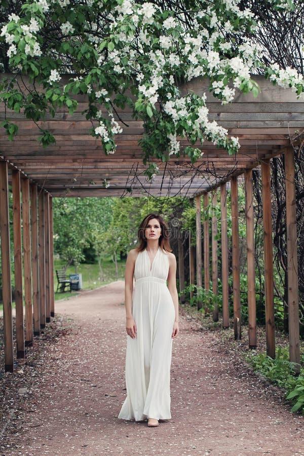 Mulher moreno lindo no vestido branco que anda no jardim da mola exterior fotos de stock