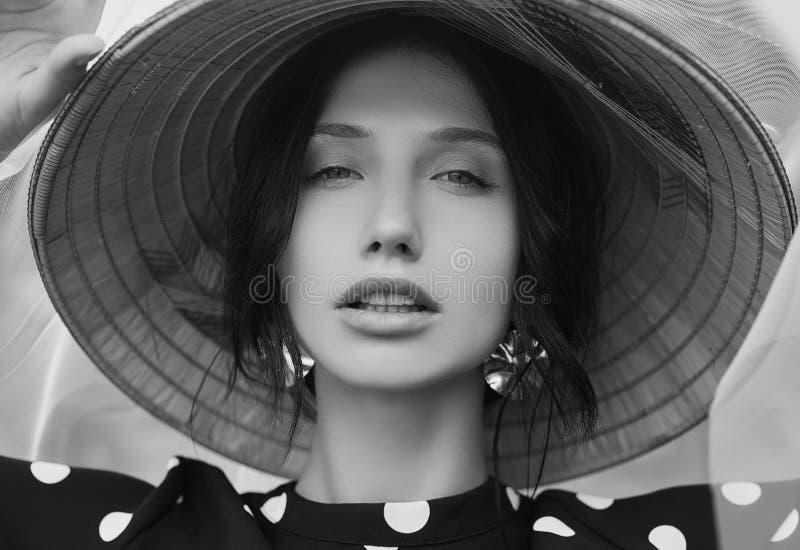 Mulher moreno lindo no vestido da forma com o chapéu do chinês da palha fotos de stock royalty free