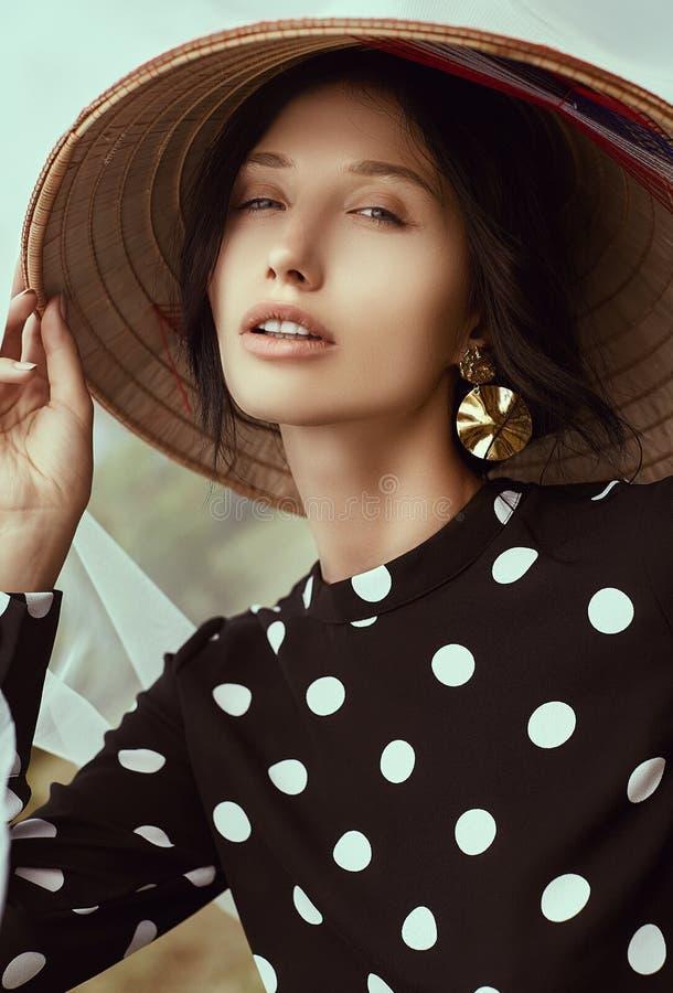 Mulher moreno lindo no vestido da forma com o chapéu do chinês da palha imagens de stock royalty free
