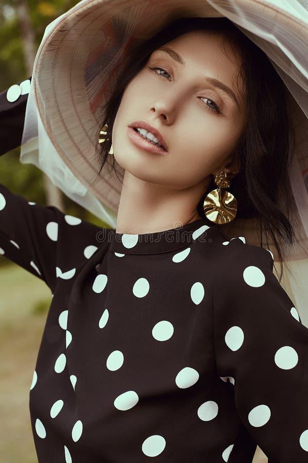 Mulher moreno lindo no vestido da forma com o chapéu do chinês da palha fotografia de stock royalty free