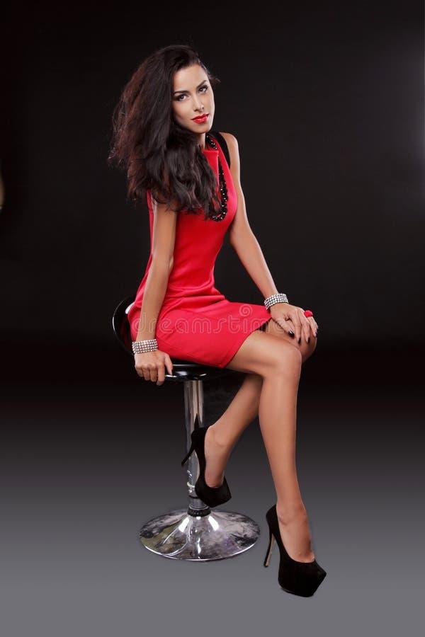 A mulher moreno lindo nova 'sexy' no vestido vermelho na cadeira, é imagem de stock