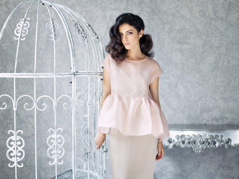 Mulher moreno na blusa cor-de-rosa e na saia cinzenta no fundo clássico do estúdio fotografia de stock royalty free