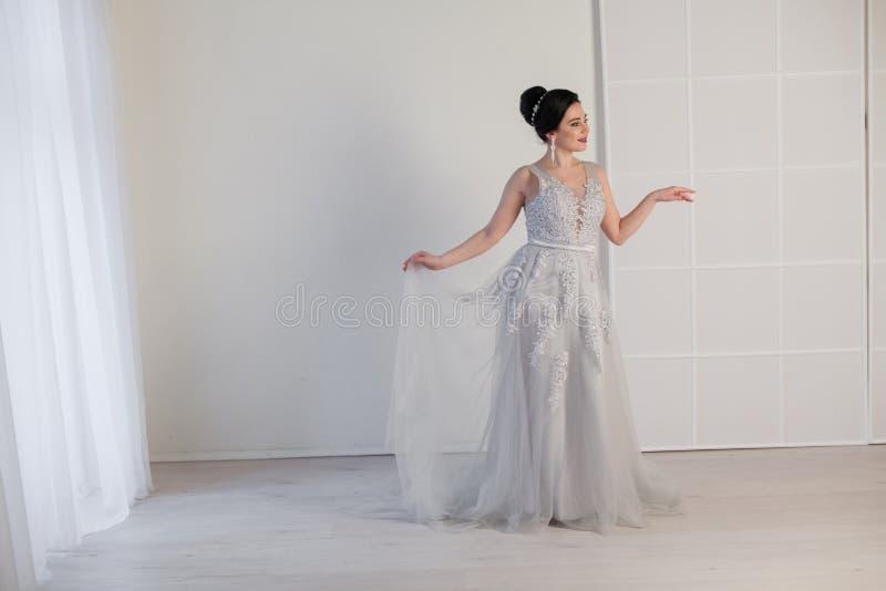 Mulher moreno no vestido de casamento cinzento fotografia de stock royalty free