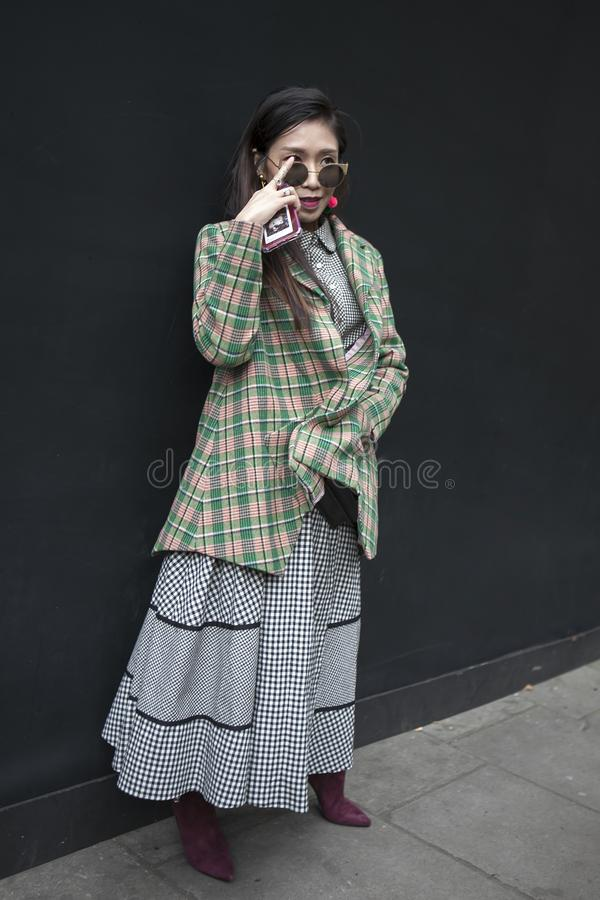 A mulher moreno nos óculos de sol e o cinza verificaram o revestimento fotografia de stock royalty free