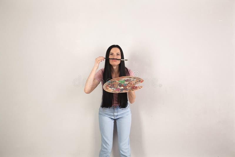 A mulher moreno nova atrativa com cabelo longo está estando pelo fundo cinzento com a paleta da pintura que tem o divertimento qu foto de stock