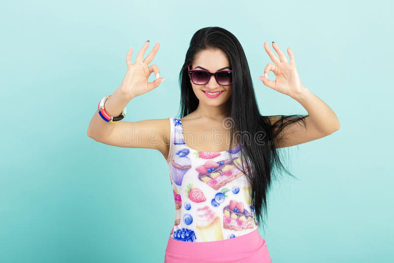 Mulher moreno nova atrativa na camiseta de alças cor-de-rosa no fundo azul menina nos óculos de sol que mostram o sinal APROVADO fotografia de stock