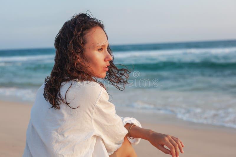 Mulher moreno nova bonita com cabelo longo em um branco em uma camisa branca no oceano no por do sol foto de stock royalty free