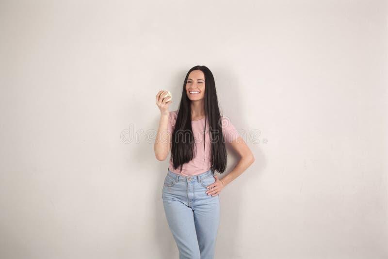 A mulher moreno nova bonita com cabelo longo está estando pelo fundo cinzento que guarda uma maçã verde em no sua mão e sorriso foto de stock royalty free