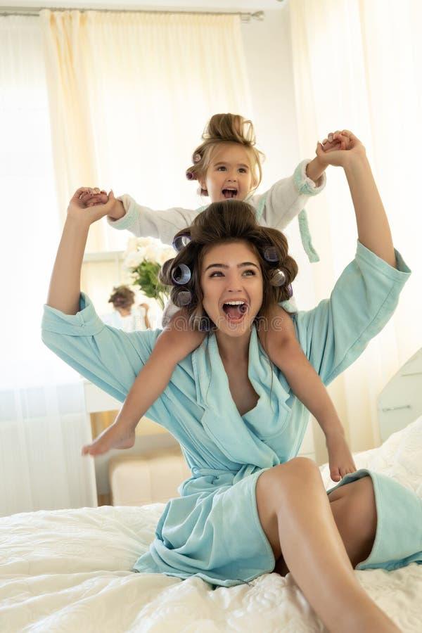 Mulher moreno nova bonita com o bebê bonito em seus ombros que vestem roupões azuis com os encrespadores que têm o divertimento s fotografia de stock