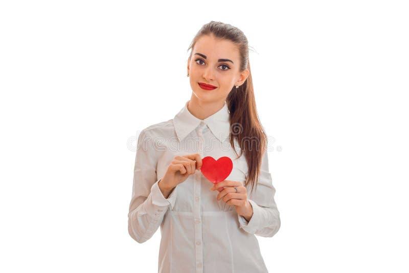 Mulher moreno nova bonita com o coração vermelho no levantamento das mãos isolado no fundo branco Conceito do dia do ` s do Valen imagem de stock royalty free