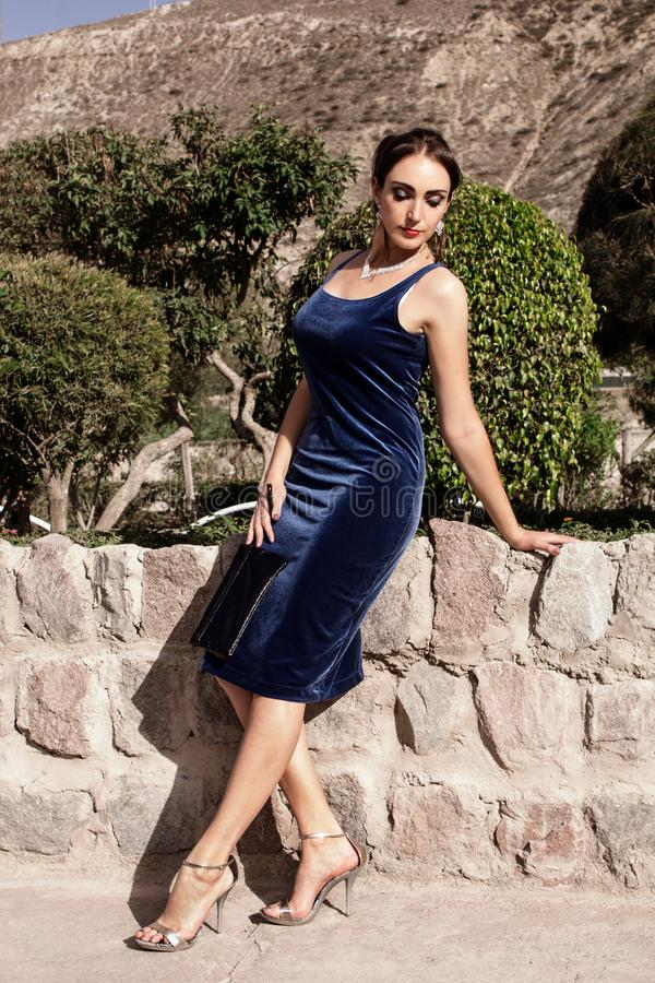 Mulher moreno nova bonita em um vestido de noite azul de veludo com uma embreagem, levantando na natureza foto de stock