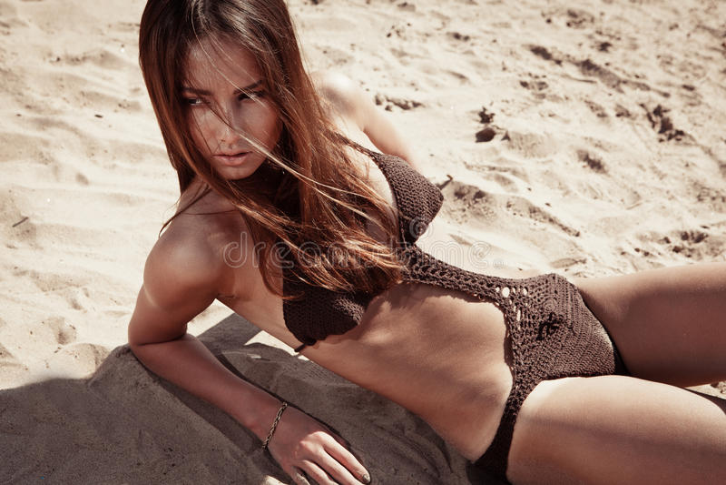 Mulher moreno nova bonita em uma praia ensolarada foto de stock royalty free