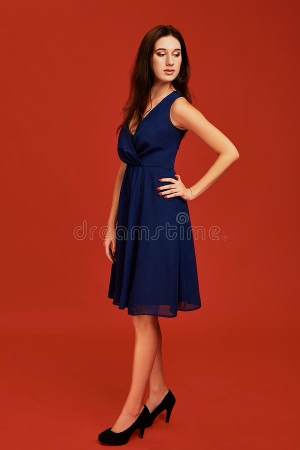 A mulher moreno nova bonita no vestido de cocktail azul elegante e nos saltos altos pretos está levantando para a câmera fotografia de stock royalty free
