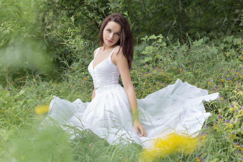 Mulher moreno nova bonita nos sundress brancos que sentam-se na grama perto da floresta em um dia de verão quente imagens de stock