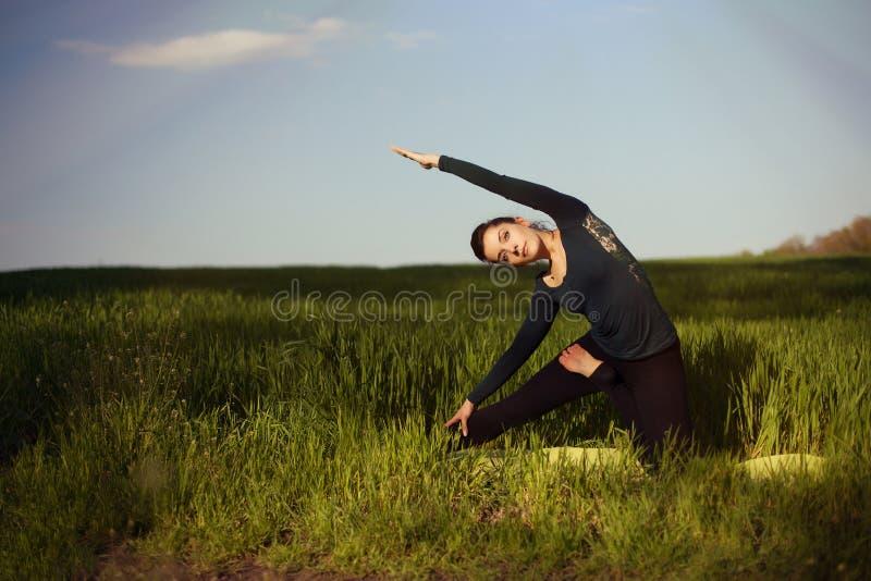 Mulher moreno nova bonita que faz a ioga em um campo do un do trigo imagens de stock royalty free
