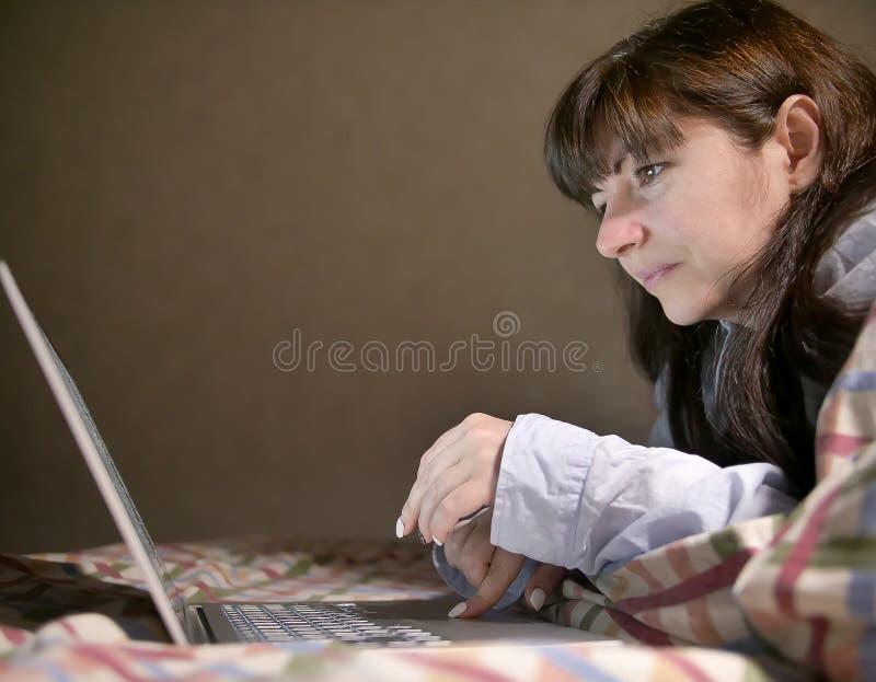 Mulher moreno nova bonito que encontra-se na cama e que datilografa em seu portátil imagem de stock