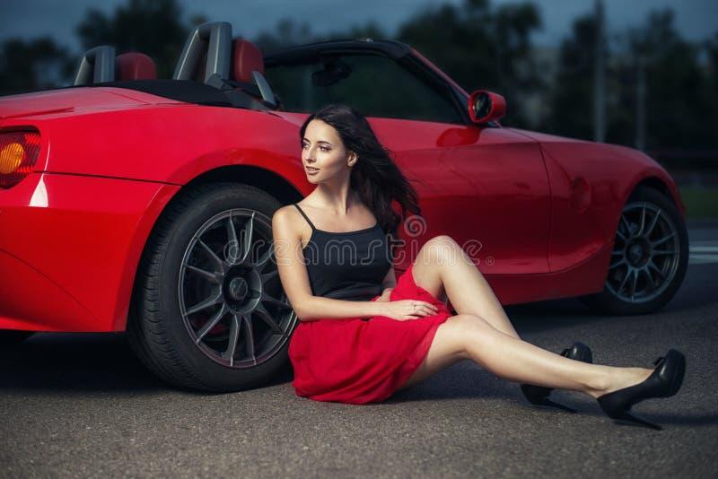 Mulher moreno nova bonito que senta-se na terra perto da roda do carro vermelho luxuoso do cabriolet foto de stock royalty free