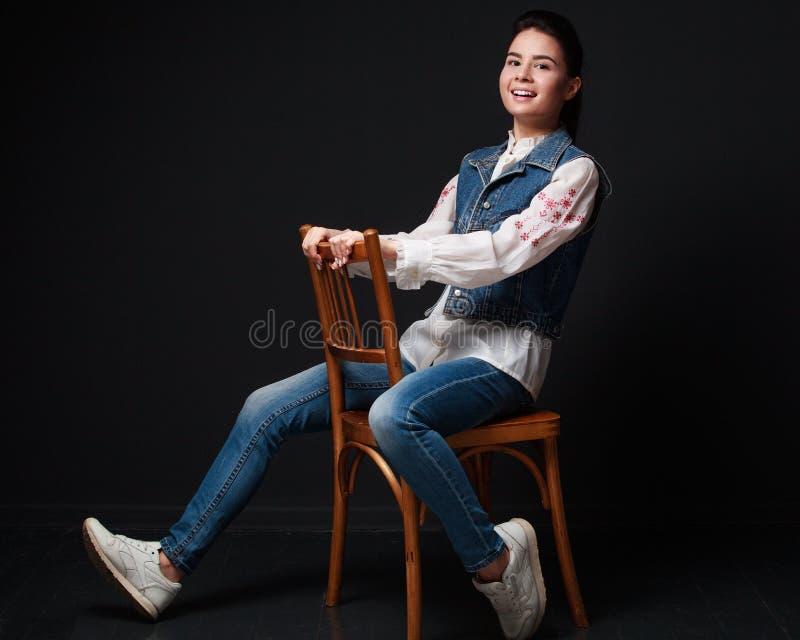 A mulher moreno nova brincalhão nas calças de brim sere o assento na cadeira imagens de stock royalty free