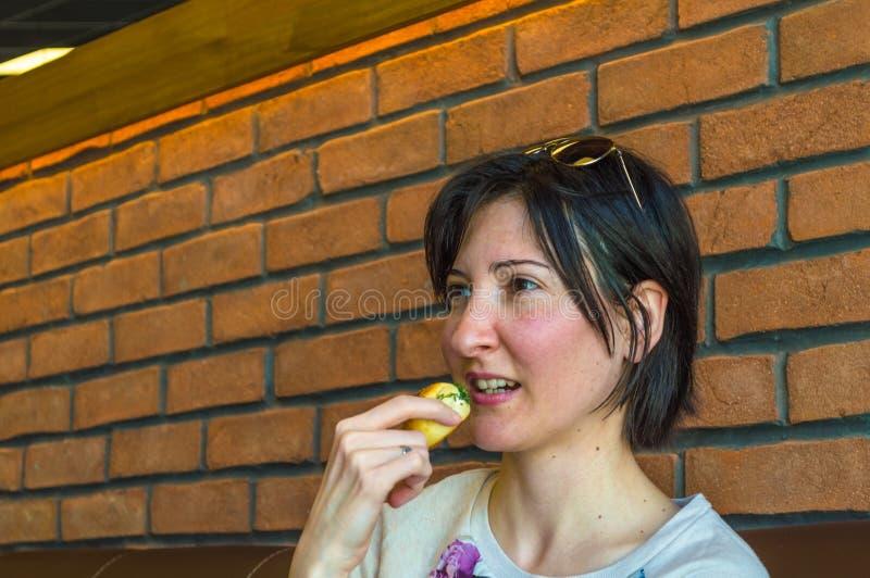 Mulher moreno nova com cabelo curto que come alguma pastelaria fotos de stock