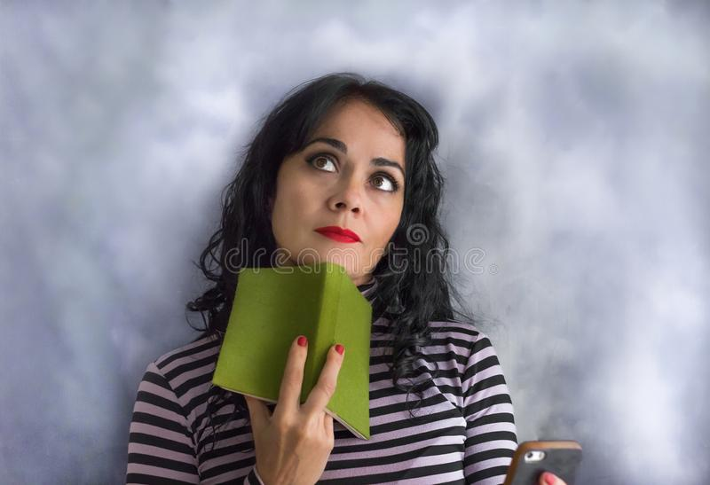 Mulher moreno nova com camiseta listrada com um livro em seu queixo que pensa sobre uma pergunta fotos de stock
