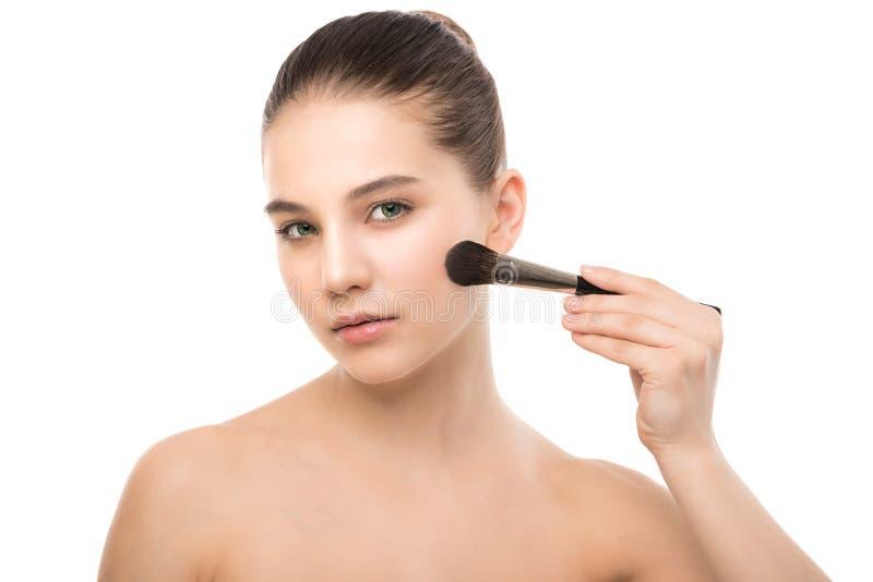 Mulher moreno nova com cara limpa Pele perfeita da menina que aplica a escova cosmética Isolado em um branco imagem de stock royalty free