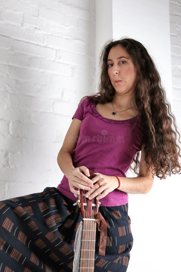 Mulher moreno nova com a guitarra acústica na saia longa Fundo da parede de tijolo fotografia de stock royalty free