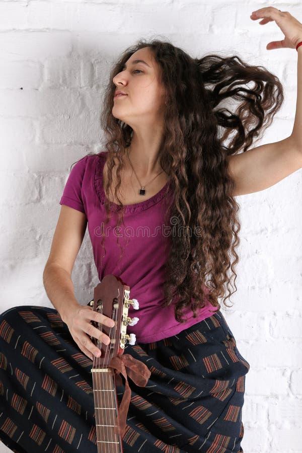 Mulher moreno nova com a guitarra acústica na saia longa Fundo da parede de tijolo imagem de stock royalty free