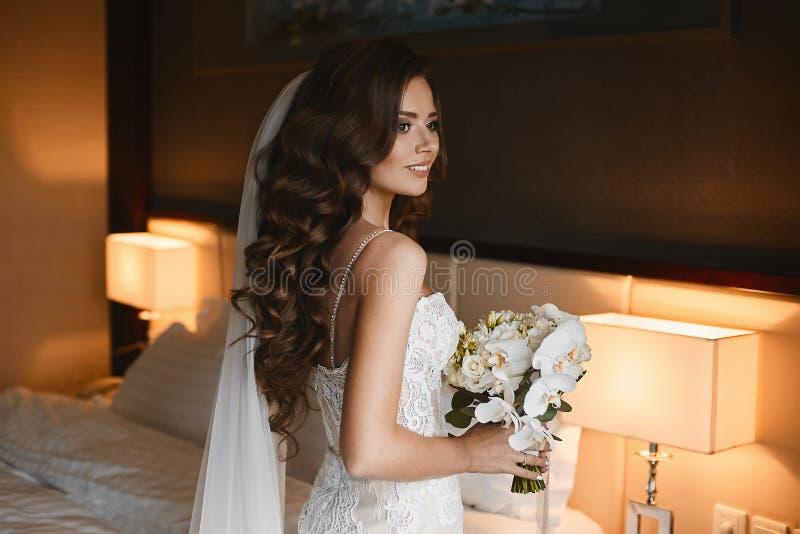 Mulher moreno nova com penteado do casamento em um vestido de casamento do laço com um ramalhete de flores frescas em suas mãos d fotos de stock