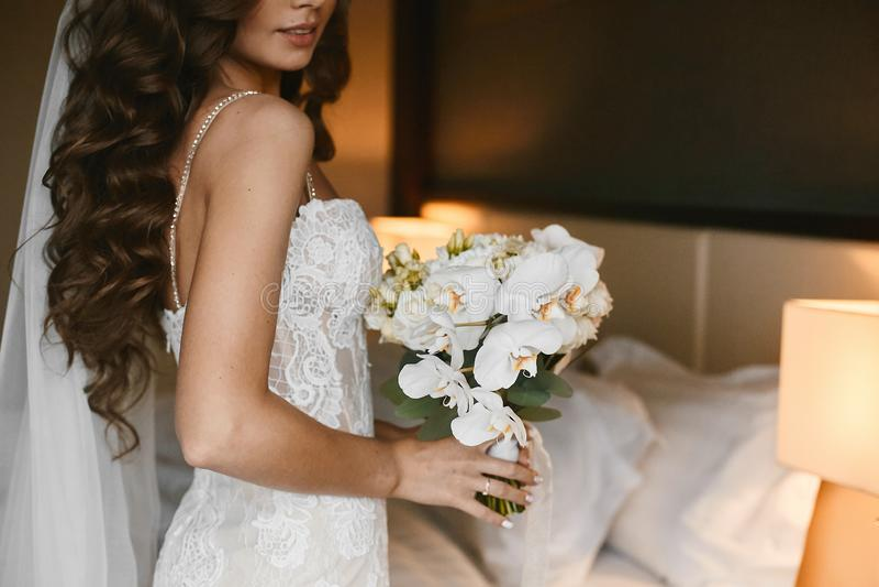Mulher moreno nova com penteado do casamento em um vestido de casamento do la?o com um ramalhete de flores frescas em suas m?os d fotografia de stock royalty free