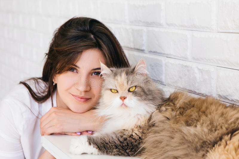 Mulher moreno nova com seu gato macio imagem de stock