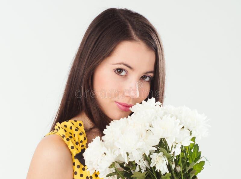 Mulher moreno nova com um ramalhete dos crisântemos brancos fotografia de stock royalty free