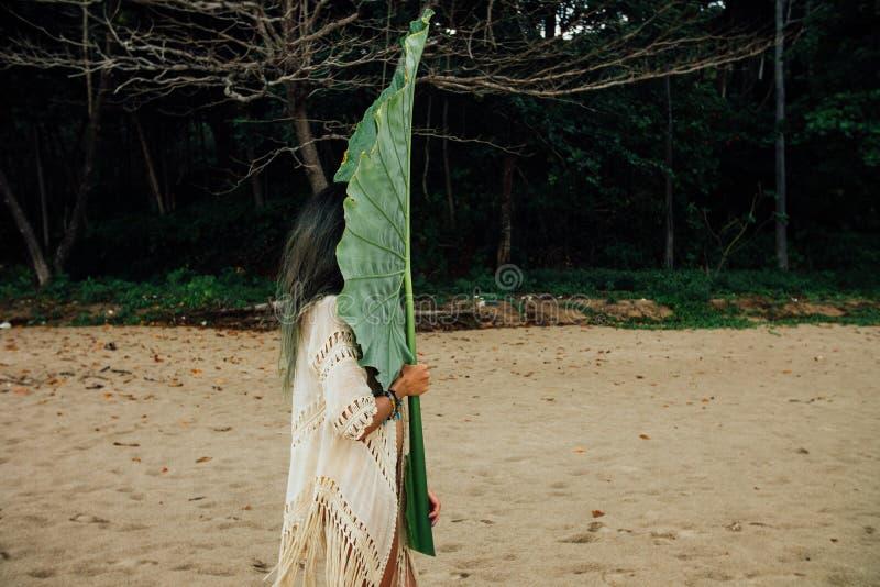 Mulher moreno nova com uma palmeira exótica da grande folha fotografia de stock