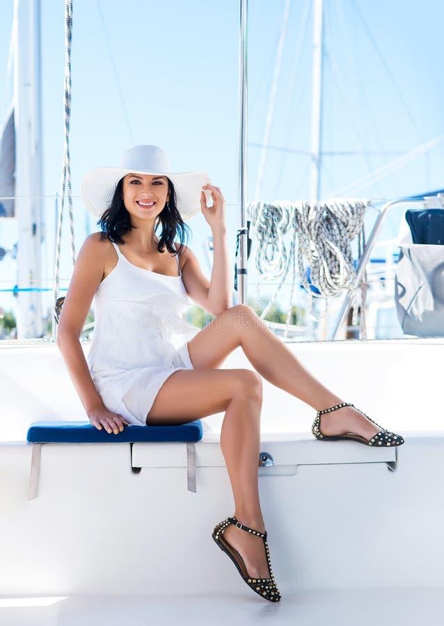 Mulher moreno nova e feliz que relaxa em um barco imagens de stock