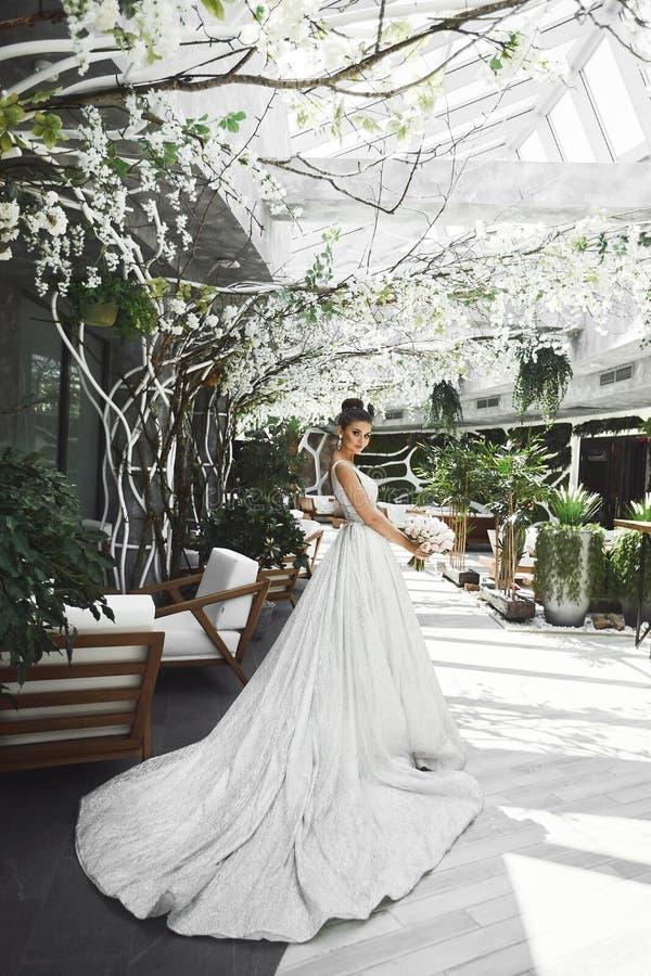 Mulher moreno nova elegante e bonita com penteado à moda nos sorrisos e no levantamento longos elegantes brancos do vestido fotografia de stock