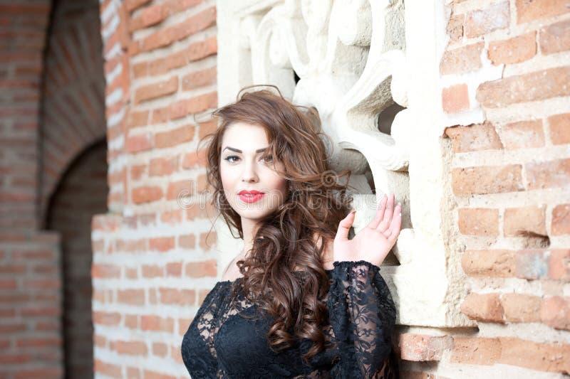 Mulher moreno nova encantador na blusa preta do laço perto de uma parede de tijolo vermelho. Jovem mulher lindo 'sexy' com cabelo  imagens de stock