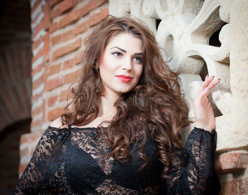 Mulher moreno nova encantador na blusa preta do laço perto de uma parede de tijolo vermelho. Jovem mulher lindo 'sexy' com cabelo  fotografia de stock