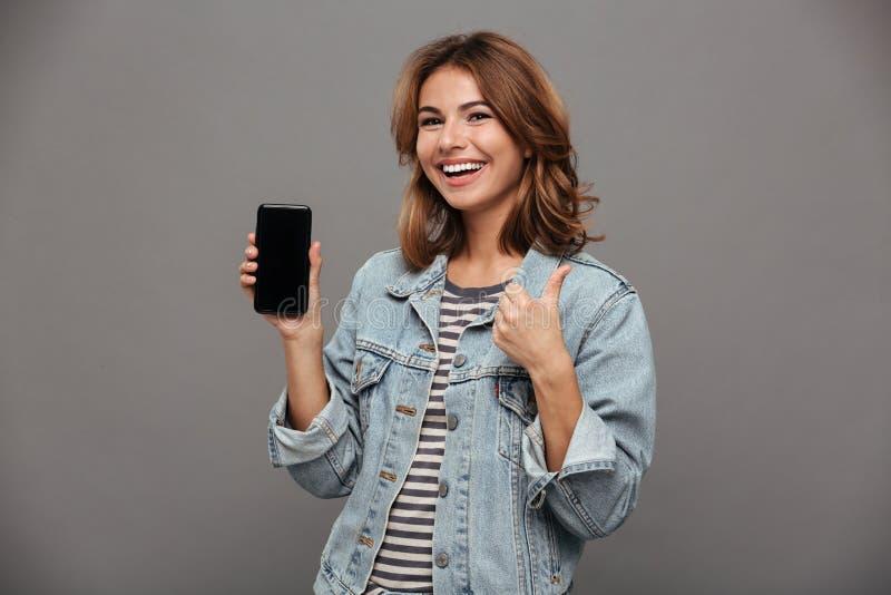 A mulher moreno nova feliz nas calças de brim veste mostrar o sc vazio do móbil imagem de stock