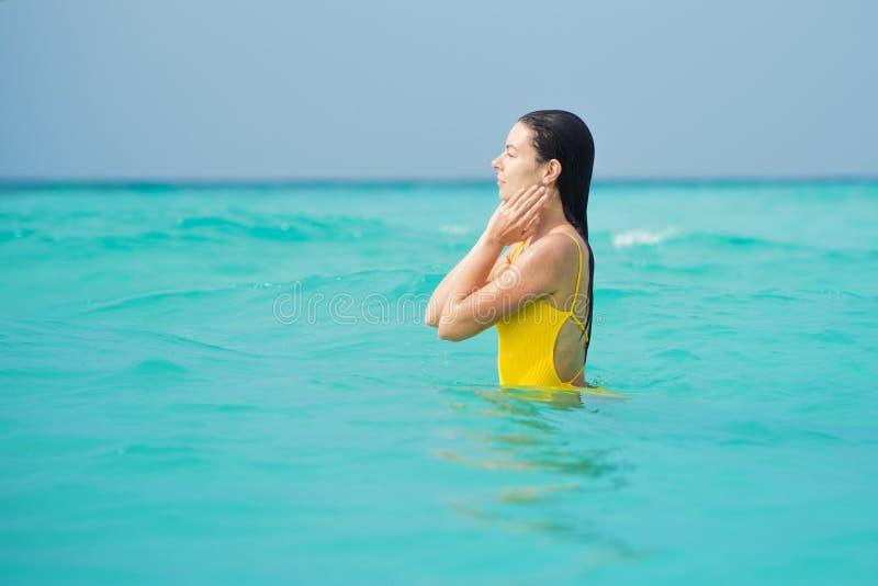 Mulher moreno nova no um roupa de banho amarelo da parte imagens de stock royalty free