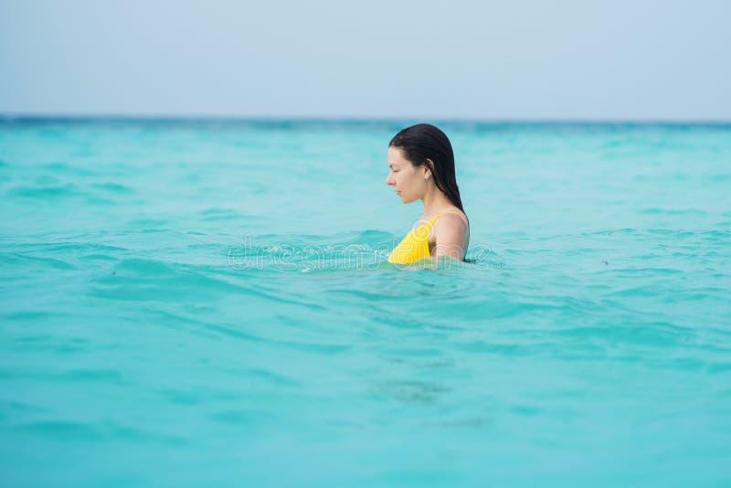 Mulher moreno nova no um roupa de banho amarelo da parte imagem de stock royalty free