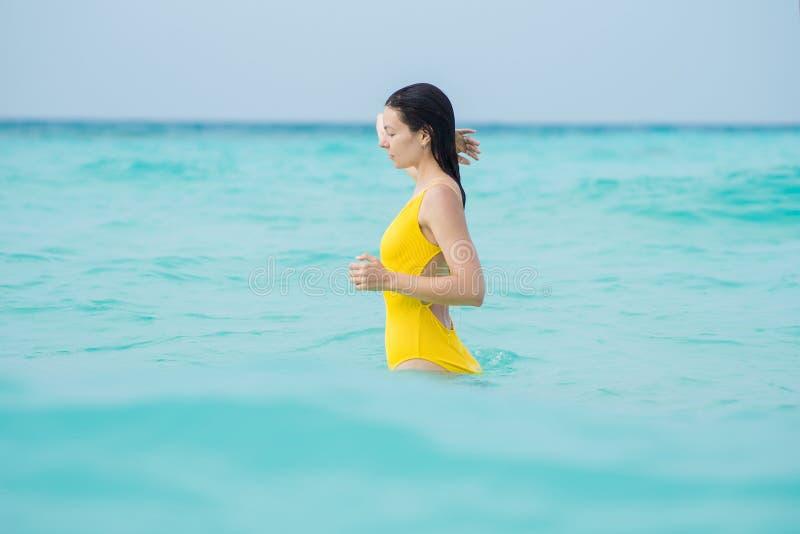 Mulher moreno nova no um roupa de banho amarelo da parte imagem de stock